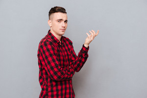 Side view of displeased young man in shirt making displeased gesture. Isolated gray background