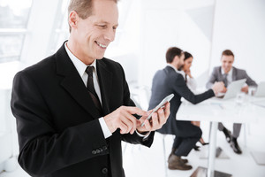 Side view of Happy Elderly Business man using phone in office with colleagues by the table on background