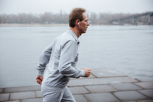 Side view of man in gray sportswear and heaphone running near the water