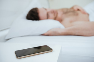 Side view of man sleeping on bed. Focus on phone lying near the bed