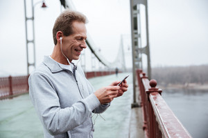 Side view of Runner in gray sportswear looking at phone and listening to music on bridge