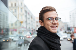 Side view of smiling business man on glasses on the street