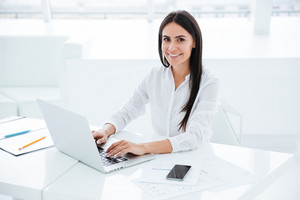 Side view of smiling business woman using laptop and looking at camera in office