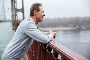 Side view of Smiling Runner in gray sportswear standing on bridge and looking away