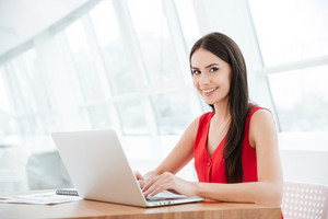 Side view of smiling woman sitting by the table with laptop in office and looking at camera