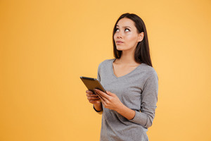 Side view of thoughtful model with tablet in studio. isolated orange background