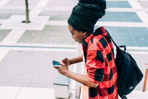 Side view of young beautiful afro black woman with typical afro hair style using smart phone hand hold wearing backpack - student, technology, social network concept