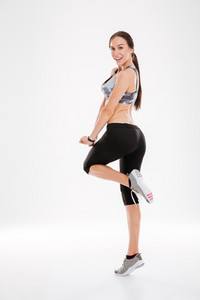Side view of young fitness woman in studio. looking at camera. full length image. isolated white background