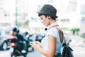 Side view of young handsome caucasian brown straight hair woman in the city holding a smart phone, headphones around her neck, looking down the screen- technology, social network, communication concept