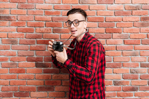 Side view of Young surprised hipster standing near the wall with retro camera in hands