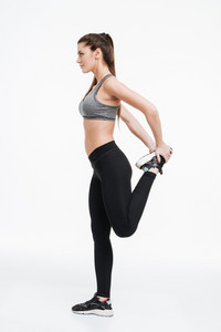 Side view portrait of a young fitness woman standing and stretching legs over white background