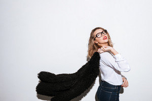 Side view portrait of a young woman in eyeglasses holding fur coat on white background