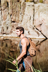 Side view portrait of an adventure man hiking wilderness mountain with backpack