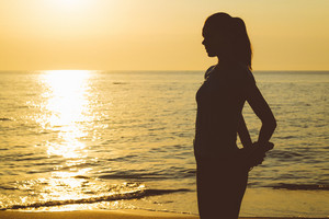 Silhouette of a slender woman on the beach during the morning exercise.