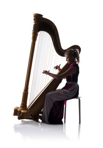Silhouette of elegant woman in dress playing the harp, isolated on white background