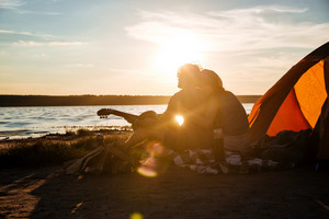 Silhouette of happy young couple sitting near touristic tent and hugging