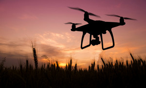 Silhouette of hovering drone taking pictures of green meadows and hills at sunset