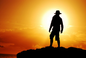 Silhouette of man in hat on the background of sunset at sea
