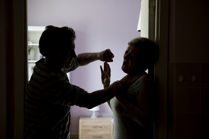 Silhouette of mature couple fighting, the man is physically abusing woman. Woman is victim of domestic violence