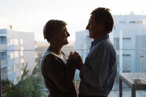 Silhouette of senior couple in love standing on a balcony against each other, holding hands, smiling