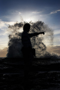 Silhouette of young man standing at the seaside