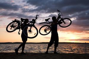Silhouettes of couple carrying their bikes while walking down seashore at sunset