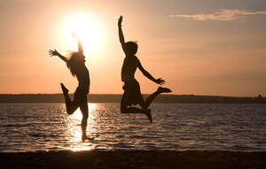 Silhouettes of happy couple jumping on background of lake at sunset