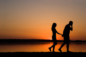 Silhouettes of man and woman holding each other by hands while walking at sunset