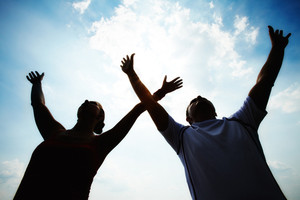 Silhouettes of sporty couple raising arms against cloudy sky