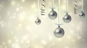 Silver Christmas ornaments over glowing background