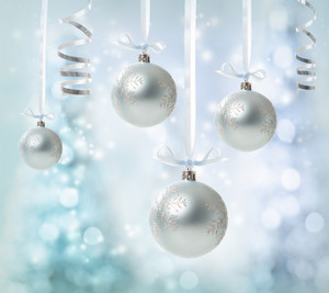 Silver Christmas Ornaments over glowing tree background