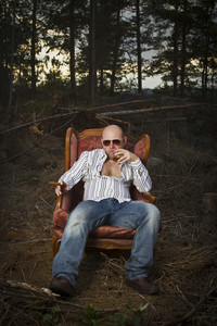 Sleazy man in a classic vintage chair in the middle of a logging area. Smoking cigar and drinking Cognac in woods.