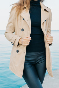 Slender girl in a beige coat and black pants on the beach, vertical framing