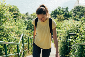 Slender girl in a yellow shirt and with backpack on the background of sea and trees. Young woman climbs the stairs in the summer.