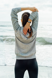 Slender woman in sportswear doing stretching on the beach in the morning