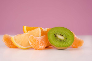 Sliced fresh peeled kiwi, lemon, tangerine and orange on a table isolated on a pink background