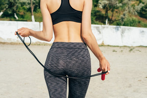 Slim girl in sportswear on the beach holding a red skipping rope, view from the back