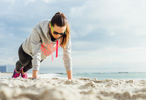 Slim girl in sun glasses and headphones does morning exercises on the beach during sunrise