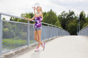 Slim woman having a break and drinks water after running