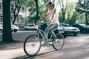 Slim woman in jeans and a T-shirt rides around town on a bicycle in summer