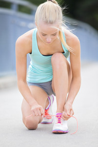 Slim woman runner tying shoelaces on bridge
