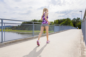 Slim woman running outdoor on bridge over a lake