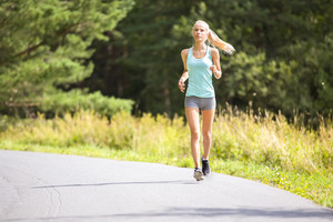 Slim young woman running on a road in the forest
