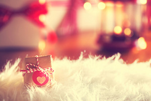 Small Christmas gift with heart tag on white carpet at night