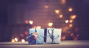 Small gift boxes on heart shaped light background