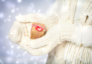 Small handmade gift box in womans hands with white gloves in the snowing night