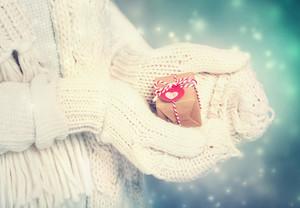 雪の夜に白い手袋で女性の手で小さな手作りのギフトボックス