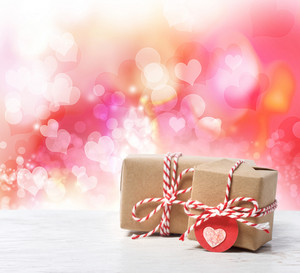 Small handmade gift boxes in pink hearts background