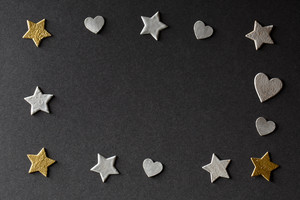 Small hearts and stars on black paper background