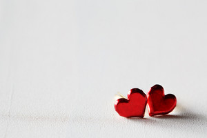 Small metal red hearts on a white wooden board